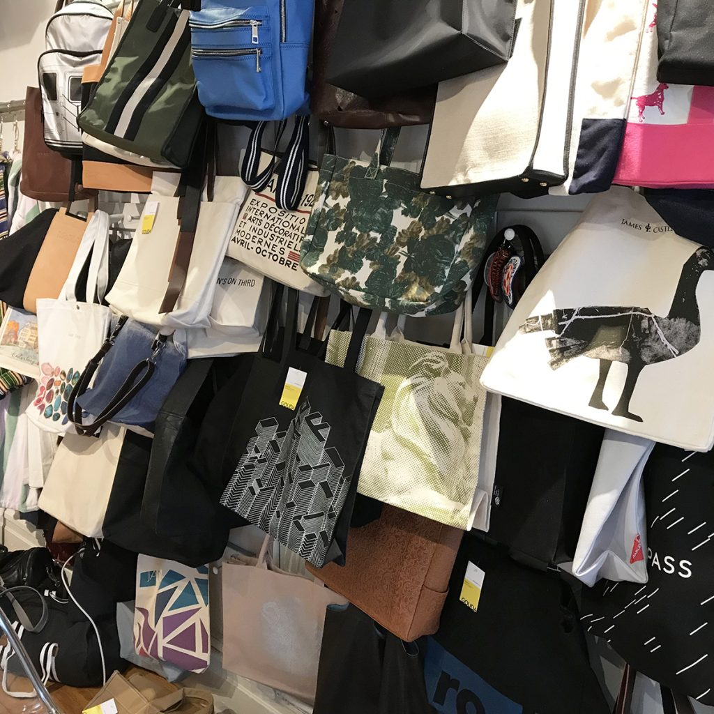 Custom bag wall in the Gouda showroom featuring leather and canvas totes